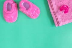 Vestiti del ` s dei bambini e bottini del bambino su fondo verde Immagine Stock