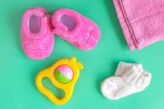 Vestiti del ` s dei bambini e bottini del bambino su fondo verde Fotografie Stock Libere da Diritti
