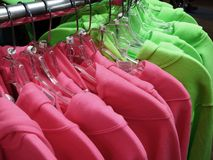 Vestiti dell'abbigliamento delle camice che appendono sul gancio dello scaffale fotografia stock libera da diritti