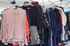 Vestiti della seconda mano che appendono su una stalla del mercato Immagini Stock