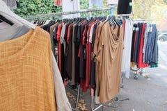 Vestiti della seconda mano che appendono su una stalla del mercato Fotografia Stock Libera da Diritti