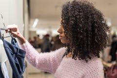 Vestiti di acquisto della donna di colore in un deposito immagini stock libere da diritti