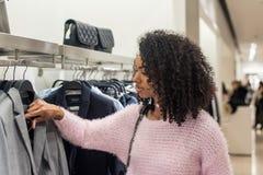 Vestiti di acquisto della donna di colore in un deposito fotografie stock