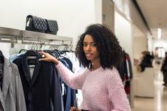Vestiti di acquisto della donna di colore in un deposito immagine stock
