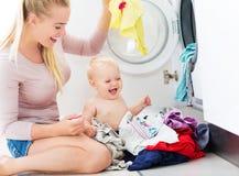 Vestiti di caricamento del bambino e della madre nella lavatrice Immagini Stock