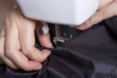 Vestiti di cucito da un singolo imprenditore Una donna sta lavorando ad una macchina per cucire Staples gli elementi del taglio d Fotografia Stock