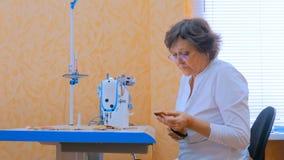 Vestiti di cucito del progettista della donna con la macchina per cucire all'atelier fotografia stock libera da diritti