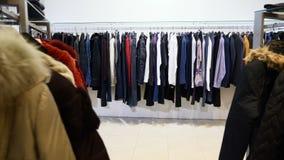 Vestiti di fucilazione per la donna e l'uomo ganci per abbigliamento in deposito all'interno Fine su abbigliamento sparato in pun stock footage