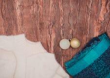 Vestiti di inverno Bello modo leggero delle signore su un fondo di legno fotografia stock