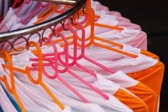 Vestiti di modo dei colori differenti sui ganci Fotografia Stock