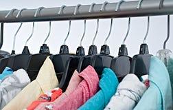 Vestiti di modo sullo scaffale dell'abbigliamento, gabinetto variopinto fotografie stock