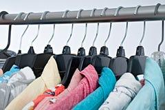 Vestiti di modo sullo scaffale dell'abbigliamento, gabinetto variopinto fotografia stock