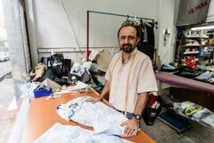 Vestiti di riparazione dell'uomo nella sua fabbrica di limitata entità Immagine Stock