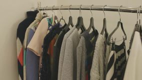 Vestiti di stilista sui ganci nel deposito video d archivio