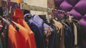 Vestiti di stilista sui ganci nel deposito stock footage