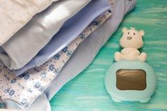 Vestiti e blu del neonato sulla stanza dei bambini di legno del fondo, gli accessori del mucchio immagini stock
