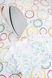 Vestiti e ferro del bambino sulla tavola da stiro su fondo variopinto con lo spazio della copia Immagini Stock