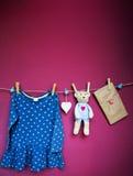 Vestiti e merci del bambino che appendono sulla corda da bucato Fotografie Stock