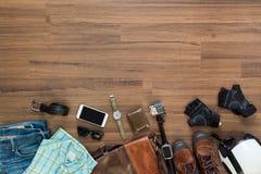 Vestiti ed accessori dei pantaloni a vita bassa su un fondo di legno Fotografie Stock