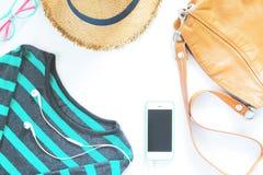 Vestiti femminili ed accessori di disposizione piana con il telefono cellulare ed il trasduttore auricolare su bianco Immagine Stock
