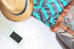 Vestiti femminili ed accessori di disposizione piana con il telefono cellulare ed il trasduttore auricolare su bianco Immagine Stock Libera da Diritti