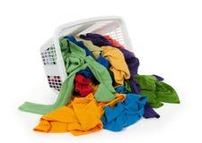 Vestiti luminosi che cadono da un cestino di lavanderia Immagini Stock Libere da Diritti