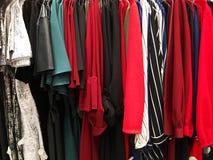 Vestiti moderni in un negozio su un gancio Camice e maglioni dei colori differenti e denim per la gioventù Fotografie Stock Libere da Diritti
