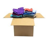 Vestiti ordinatamente piegati in grande scatola isolata Fotografie Stock