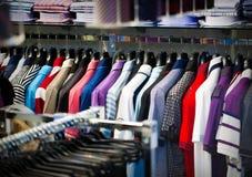 Vestiti per gli uomini su un gancio in negozio Immagine Stock