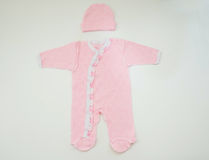 Vestiti per la ragazza neonata su fondo bianco Fotografia Stock