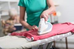 Vestiti rivestenti di ferro dell'assistente domestico per una donna anziana fotografia stock