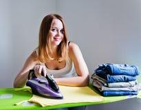 Vestiti rivestenti di ferro della bella donna felice. Lavoro domestico fotografia stock