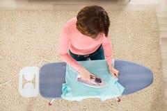 Vestiti rivestenti di ferro della donna con il ferro di vapore Immagine Stock Libera da Diritti