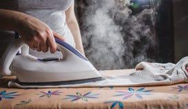 Vestiti rivestenti di ferro sulla tavola da stiro Immagini Stock