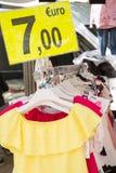 Vestiti sulla vendita che appende sullo scaffale con un'etichetta di sconto Fotografia Stock