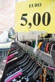 Vestiti sulla vendita che appende sullo scaffale con un'etichetta di sconto Immagini Stock