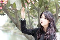 Vestiti teenager dal nero della ragazza dello studente tailandese i bei si rilassano in parco fotografia stock libera da diritti