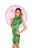 Vestito asiatico dalla donna capa di rosso con l'ombrello dietro lei Fotografie Stock Libere da Diritti