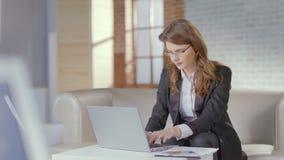 Vestito attraente dalla donna che funziona nell'ufficio, facendo uso del computer portatile stock footage