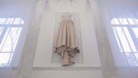 Vestito beige da nozze che appende sulla parete dentro la stanza dello spazio in grande casa stock footage