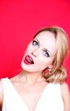 Vestito bianco d'uso dalla donna caucasica su fondo rosso che lecca le sue labbra Fotografie Stock