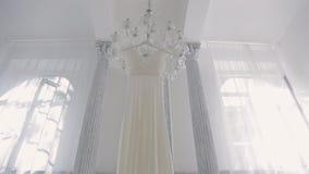 Vestito bianco da nozze che appende sul candeliere dentro la stanza dello spazio video d archivio