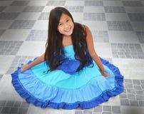 Vestito colourful d'uso di seduta dalla ragazza graziosa   immagini stock libere da diritti