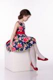 Vestito d'uso dalla bambina con i fiori isolati su fondo bianco Sta sedendosi sul cubo Colpo dello studio fotografie stock