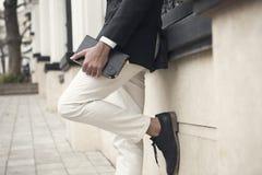 Vestito d'uso dell'uomo elegante che posa contro una parete immagine stock libera da diritti