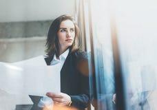 Vestito d'uso della donna di affari del ritratto, smartphone di conversazione e carte di tenuta in mani Ufficio del sottotetto de Fotografie Stock Libere da Diritti