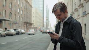 Vestito d'uso sorridente felice dell'uomo d'affari e per mezzo dello smartphone moderno vicino all'ufficio al primo mattino, rius archivi video