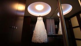 Vestito da sposa bianco che appende nella stanza scura archivi video