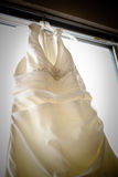 Vestito da sposa che appende nella finestra Immagini Stock Libere da Diritti
