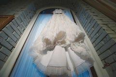 Vestito da sposa che appende nella finestra, pizzo Immagine Stock Libera da Diritti